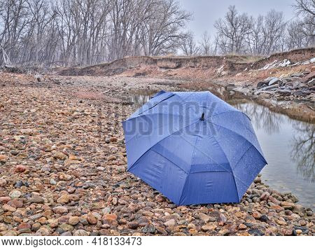umbrella on a river shore in early spring scenery with a low water and falling snow