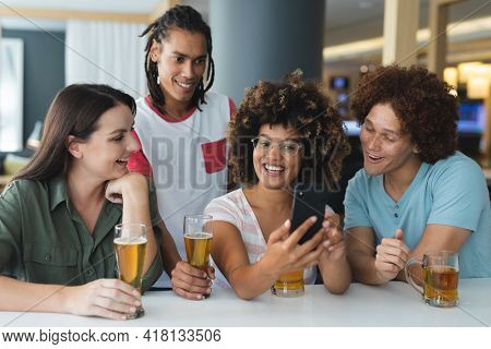 Diverse group of male and female friends looking at smartphone at bar. friends socialising and drinking at bar.