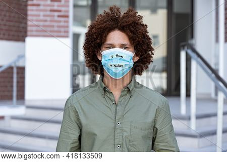 Portrait of mixed race man wearing a face mask with writing. equal rights and justice protestors on demonstration march during coronavirus covid 19 pandemic.
