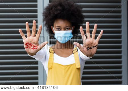 Portrait of mixed race woman wearing face mask making stop gesture with hands covered in writing. equal rights and justice protestors on demonstration march during coronavirus covid 19 pandemic. .