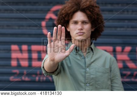 Portrait of mixed race man holding hand making a stop gesture. equal rights and justice protestors on demonstration march.