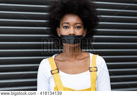 Portrait of mixed race woman having black tape on mouth. equal rights and justice protestors on demonstration march.