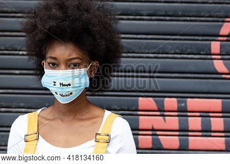 Portrait of mixed race woman wearing a face mask with writing. equal rights and justice protestors on demonstration march during coronavirus covid 19 pandemic.