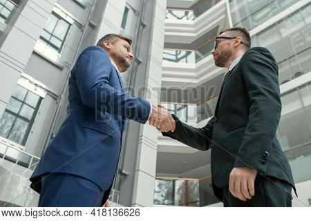 Below view of male lawyers in formal wear standing in hall of commercial center and making handshake as symbol of partnership