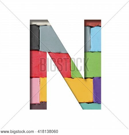 Multi-colored Plasticine Font. Letter N Cut Out Of Paper On A Background Of Pieces Of Colored Plasti