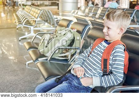 Happy Junior Schoolboy With Orange Backpack Sits Waiting For Flight On Comfortable Chair In Spacious