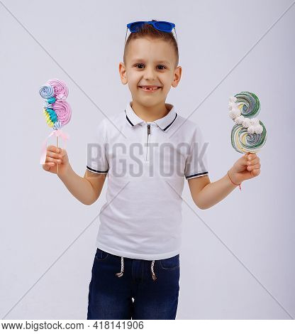 A Boy In Sunglasses On A White Background Holds A Figure Eight Candy. Womens Day, Congratulations. M