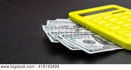 Calculator With Dollar Bills On Black. Close Up.