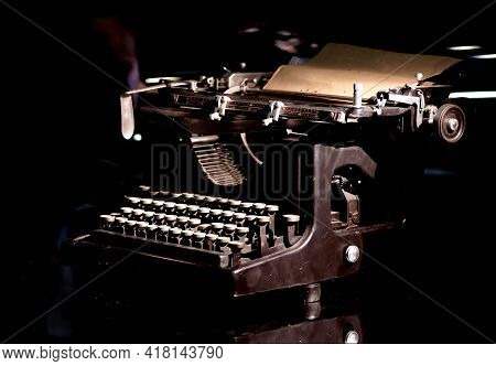 Vintage mechanical typewriter with installed paper sheet on black background concept photography close-up view