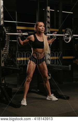 A Sporty Woman With Blonde Hair Is Squatting With A Barbell Near The Squat Rack In A Gym. A Girl Is