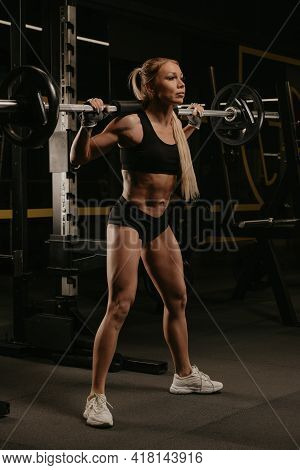 A Sporty Woman With Blonde Hair Is Started Squatting With A Barbell Near The Squat Rack In A Gym. A
