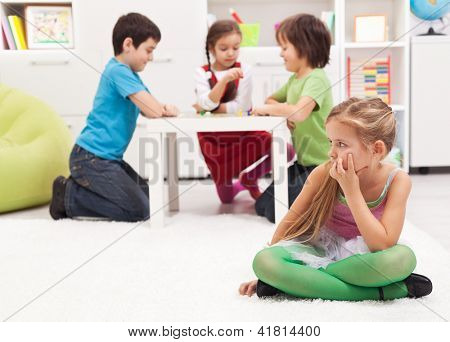 Little girl sitting lonely - feeling excluded by the others