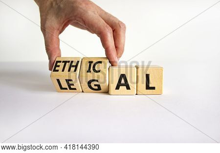 Ethical Or Legal Symbol. Businessman Turns Wooden Cubes And Changes The Word 'legal' To 'ethical' On
