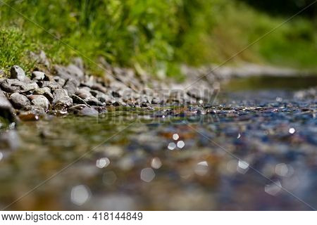 A Stream Flows Along The Street, A Sewer Breakthrough, Water Flows Between Stones And Grass