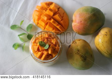 Vanilla Custard Topped With Fresh Cut Mangoes Served In A Jar.