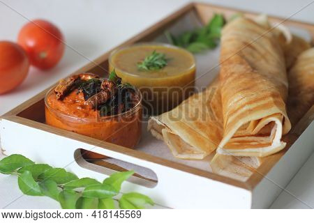 Crispy Pancake Made Of Rice And Lentils. Served With Tomato Chilly Condiment And Sambar.