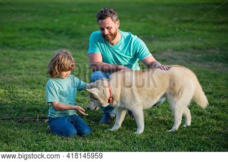 Smiling Father And Son With Pet. Happy Family With Loyal Pedigree Dog Have Fun At The Backyard.