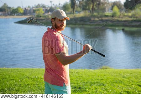 Golfer Playing Golf In The Evening Golf Course. Man Playing Golf On A Golf Course In The Sun.