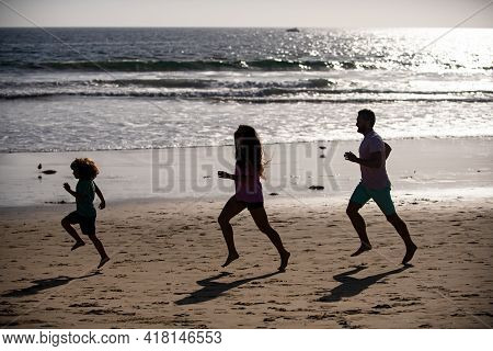 Joggers Family Have Fun On Beach Run And Jump At Sunset. Father, Mother, Baby Son Run. Child Jump Wi