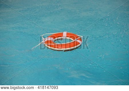 No Swimming. Water Rescue Emergency Equipment. Rescue Ring Floating In Clear Pool Water. Summer.