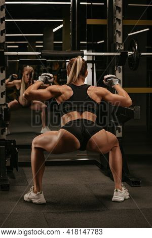 A Photo From Behind Of A Sporty Woman With Blonde Hair Who Is Warming Up Before Squatting With A Bar