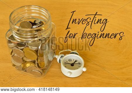 Phrase Investing For Beginners Written On Board With Clock And Coins. Business Concept. Selective Fo