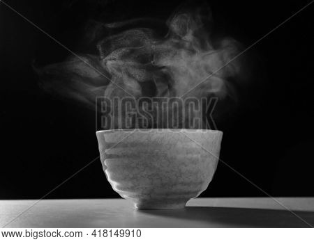 Bowl With Steam On Table Against Black Background