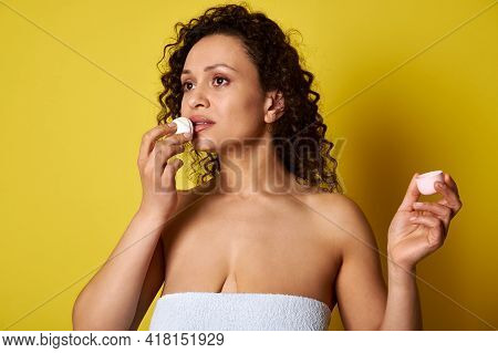 A Young Woman Wrapped In A Bath Towel Using A Hygienic Lipstick For Hydrating And Taking Care About