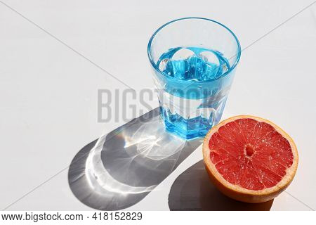 Summer Still Life With Blue Glass Of Cold Water And Half Of Grapefruit On White Table Background. To