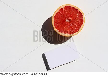 Summer Still Life With Half Of Grapefruit And Blank Paper Card On White Background. Mockup Invitatio