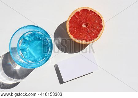 Summer Still Life With Glass Of Water, Half Of Grapefruit And Blank Paper Card On White Background.