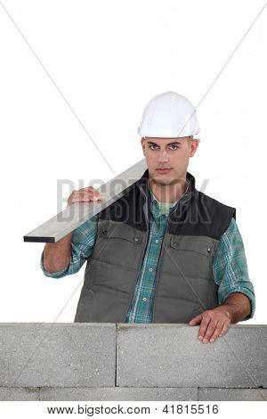 Builder stood by uncompleted wall