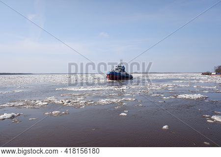 A Tugboat Sails Along A Large Full-flowing Spring River During The Ice Drift. Sunny Day, Blue Sky.