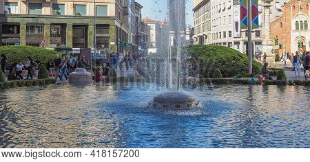 Milan, Italy - March 28, 2015: Tourists By Piazza San Babila Fountain In Milan City Centre