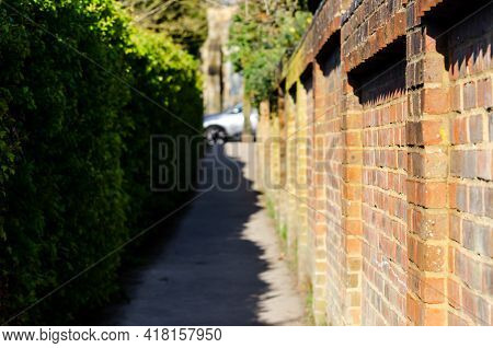 Narrow Mysterious Brick Wall Alleyway Towards St. Nicolas Church In Barton Le Clay