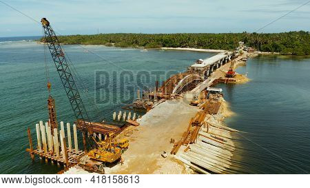 Pile Hammer Working On Construction Site. Bridge Under Construction Over The Sea Bay Connecting The