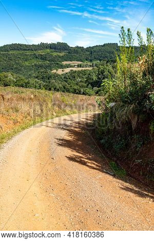 Dirty Road With Farm Fields, Forest And Mountains