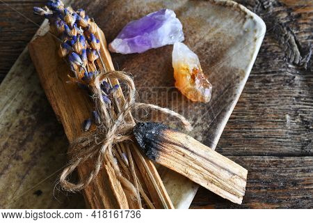 A Close Up Image Of Sacred Holy Wood With Dried Lavender And Healing Crystals On A Hand Made Pottery