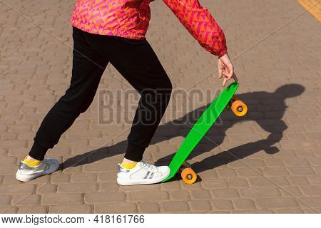The Girl Is Riding A Skateboard Or Penny Board In The Park. The Child Is Dressed In Bright Clothes A
