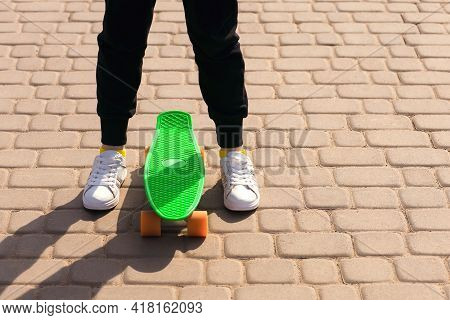 A Teenager Learns To Ride A Skateboard Or Penny Board. Legs And Skateboard Close Up. Free Space For