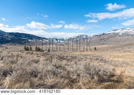 Okanagan Valley Natural Grasslands With Snow-capped Mountains And Blue Sky
