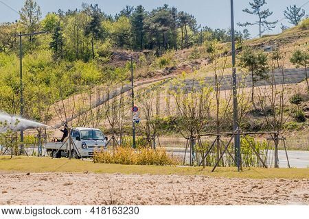 Daejeon, South Korea; April 18, 2021: Unidentified Man In Back Of Truck Spraying Water On Newly Plan