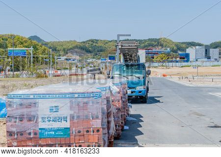 Daejeon, South Korea; April 18, 2021: Pallets Of Red Bricks Covered With Plastic On Side Of Road At
