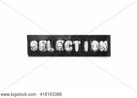 Embossed Letter With Word Selection In Black Banner On White Paper Background
