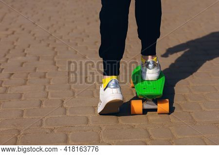 Girl Teenager Rides A Skateboard Or Penny Board In The Park. The Child Is Dressed In Bright Clothes