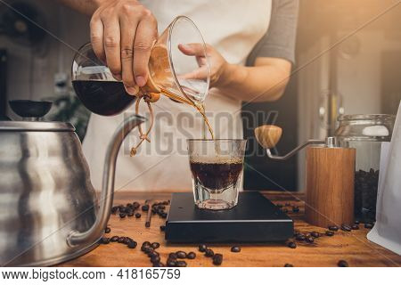Barista Holding Coffee Drip Jug Pour Coffee To Glass Cup. Making Filter Coffee. Drip Coffee.