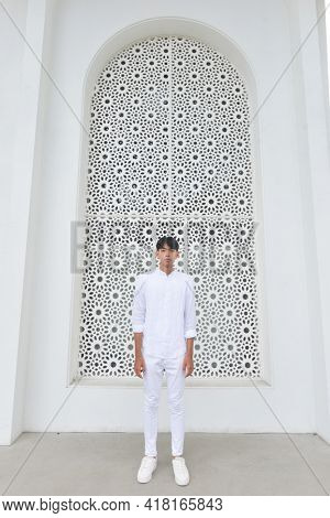 profile shot of a Fashion style photo of a handsome man  in white shirt and white pants , posing on white building