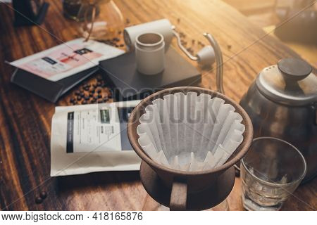 Close Up Filter Coffee On Wooden Table With Zipper Bag Coffee. The Process Of Making Drip Coffee.