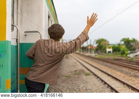 Handsome Young Asian Man Hand To Say Hello Or Goodbye To Friend On Train, Waving Goodbye