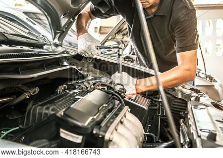 Car Care Maintenance And Servicing, Close-up Hands Of Auto Mechanic Are Using The Wrench To Repairin
